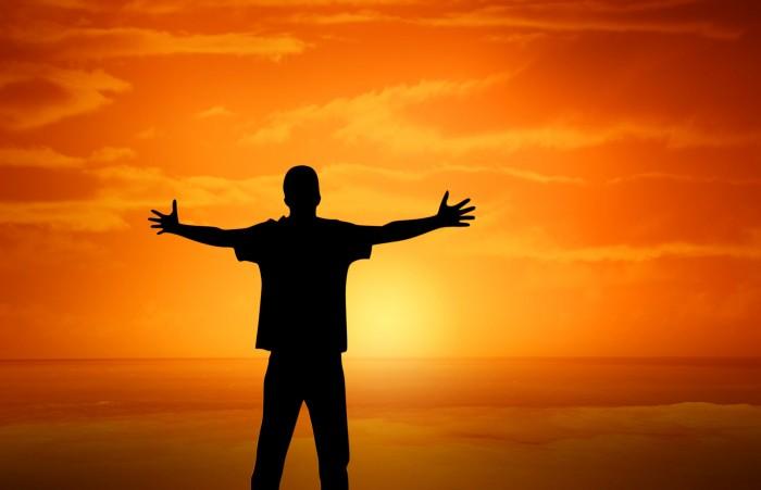 człowiek na tle zachodzącego słońca